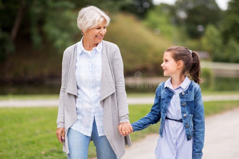 Grandmother and granddaughter walking at park stock photos