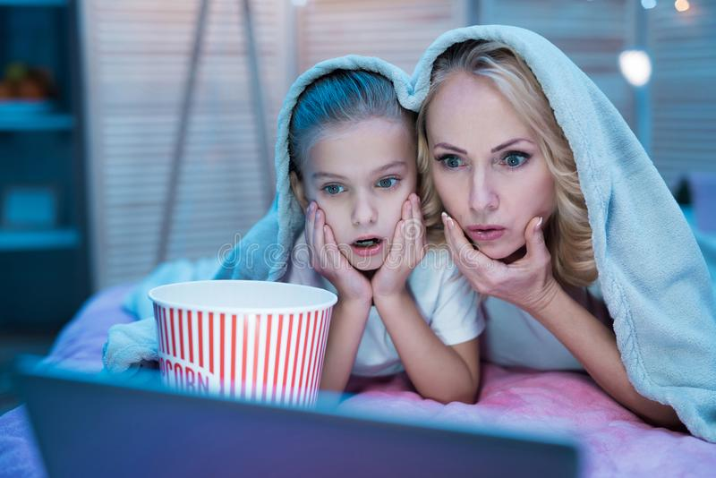 Grandmother and granddaughter are watching movie on laptop under blanket at night at home. royalty free stock image