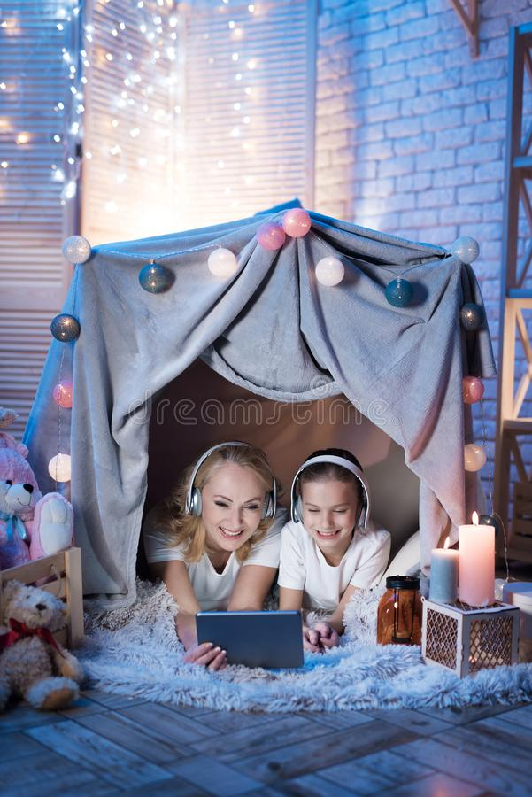Grandmother and granddaughter are watching movie on tablet in blanket house at night at home. royalty free stock image