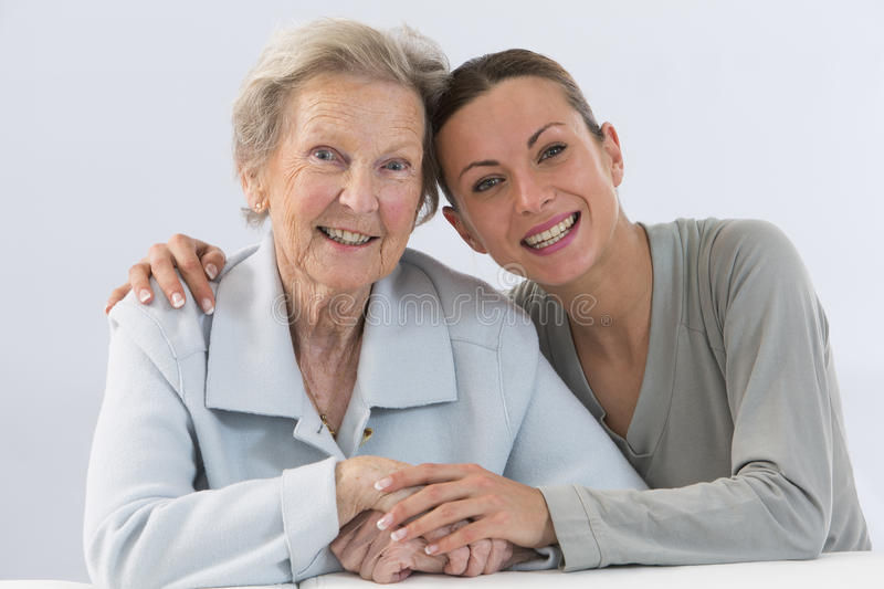 Grandmother and granddaughter. Young women takes care of an elderly woman royalty free stock images