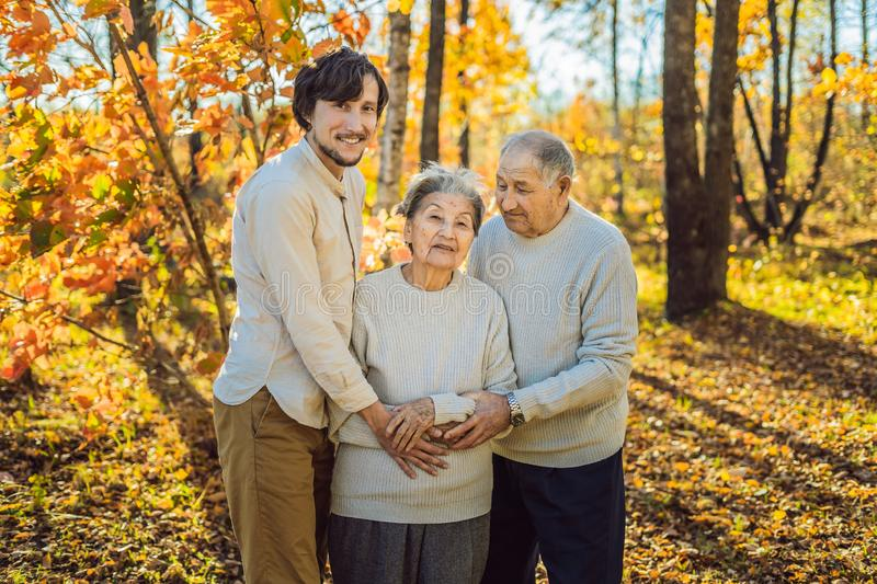 Grandmother, grandfather and adult grandson hugging in autumn park.  stock image