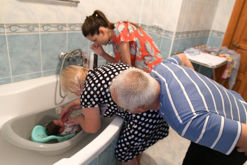 Grandmother and grandfather bathe the child, his grandson. Happy family: grandparents with their grandson. first bathing at home.  stock photo