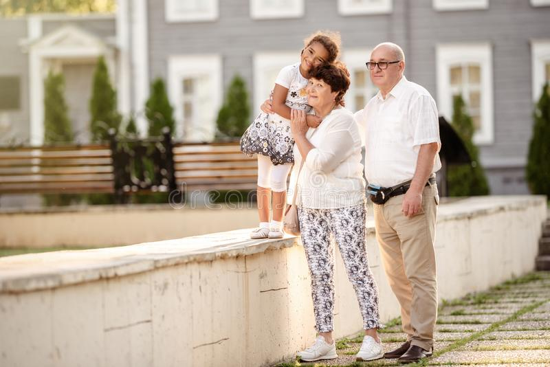 Portrait of adorable grandparents with her cute granddaughter walking in the park. Happy grand mother and grand father holding on royalty free stock images