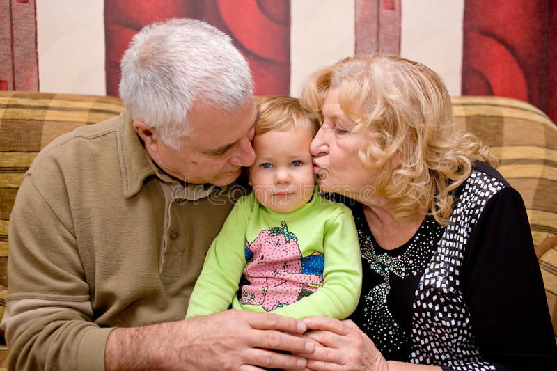 Grandmother and grandfather kissing baby stock images