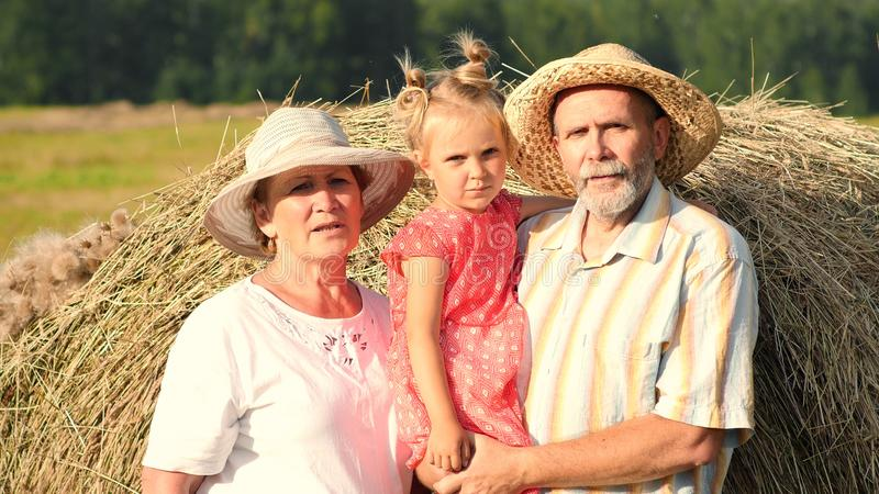 Grandparents with little granddaughter in the meadow. Grandmother, grandfather and little granddaughter stand near haystack in the meadow at golden hour. Family stock photo