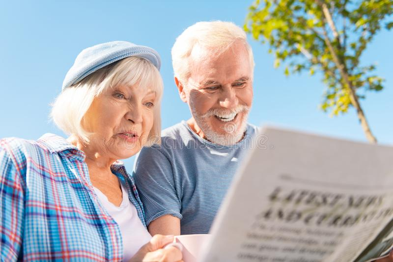 Grandmother and grandfather seeing story about their grandchildren in newspaper royalty free stock photo