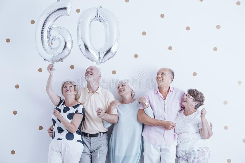 Grandmother and grandfather with silver balloons celebrating 60th birthday stock photography