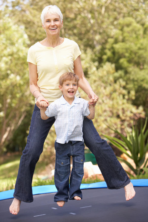 Grandmother And Grandson Jumping On Trampoline In Stock Photos