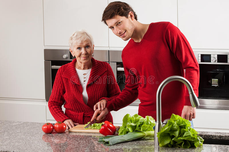 Grandmother with grandson in kitchen. Grandmother with adult grandson cooking together in kitchen stock images