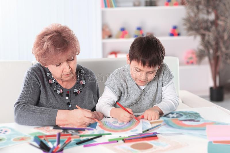 Grandmother and grandson paint a rainbow in the nursery royalty free stock photo