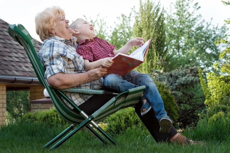 Grandmother and grandson reading a book outdoors.Funny stories. royalty free stock image