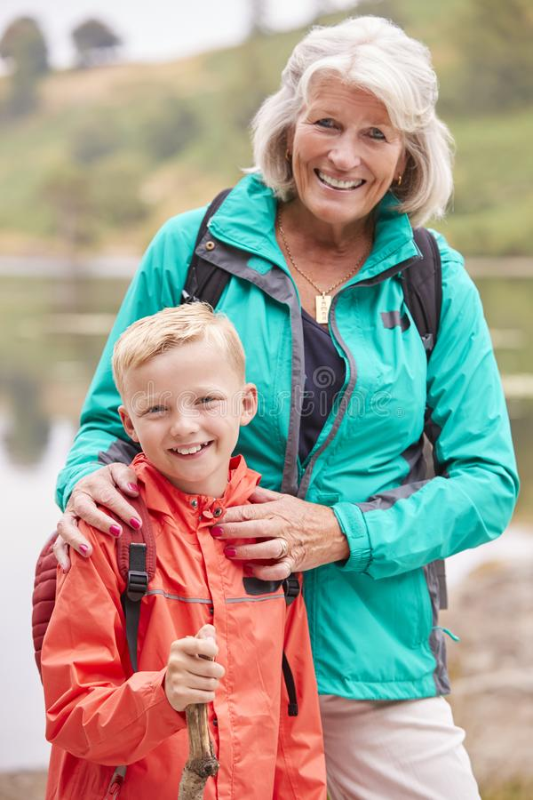 Grandmother and grandson standing together near a lake in the countryside smiling to camera, close up, Lake District, UK stock image