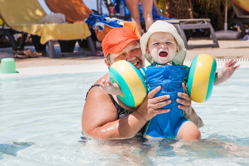 Grandmother and grandson swimming together in the pool. Outdoor, summer royalty free stock photo