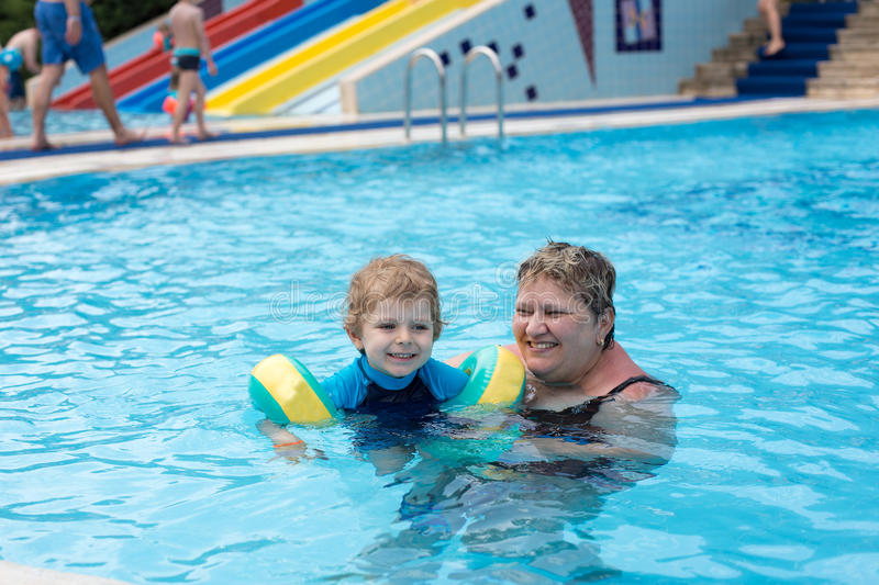 Grandmother and grandson swimming together in the pool. Outdoor, summer royalty free stock image