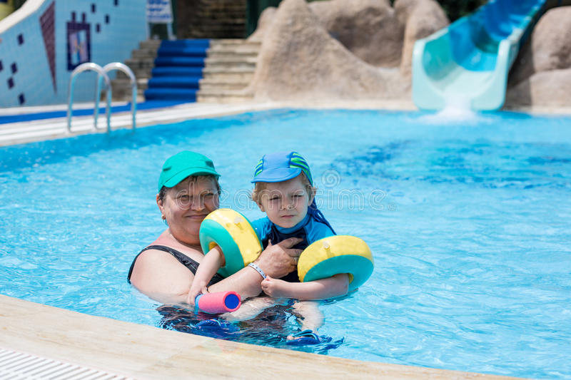 Grandmother and grandson swimming together in the pool. Outdoor, summer royalty free stock photos
