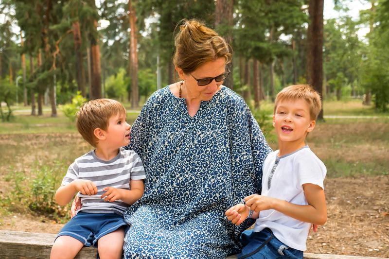 Two cute boys talking with nurse, grandmother. Kids laughing in the park, garden, forest. One parent family. Siblings royalty free stock photography