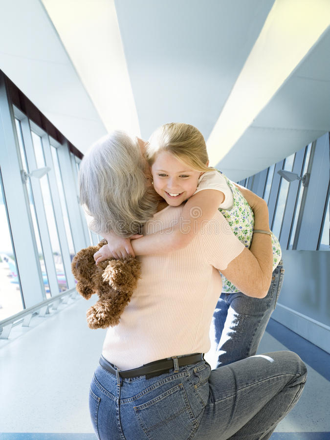Grandmother greeting and hugging granddaughter at airport royalty free stock photography