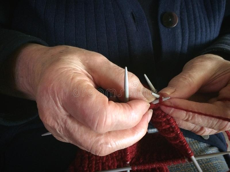 Grandmother hands knit red wool yarn. Senior lady, granny in blue knitted sweater handmade. needle pattern from thread loop. cl royalty free stock photo