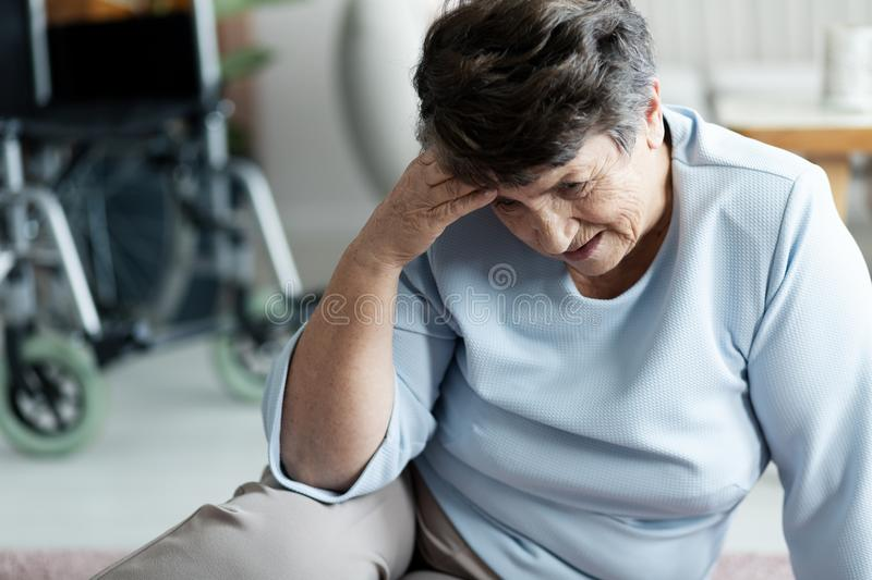 Grandmother with headache after falling on the floor. In the nursing house royalty free stock photo