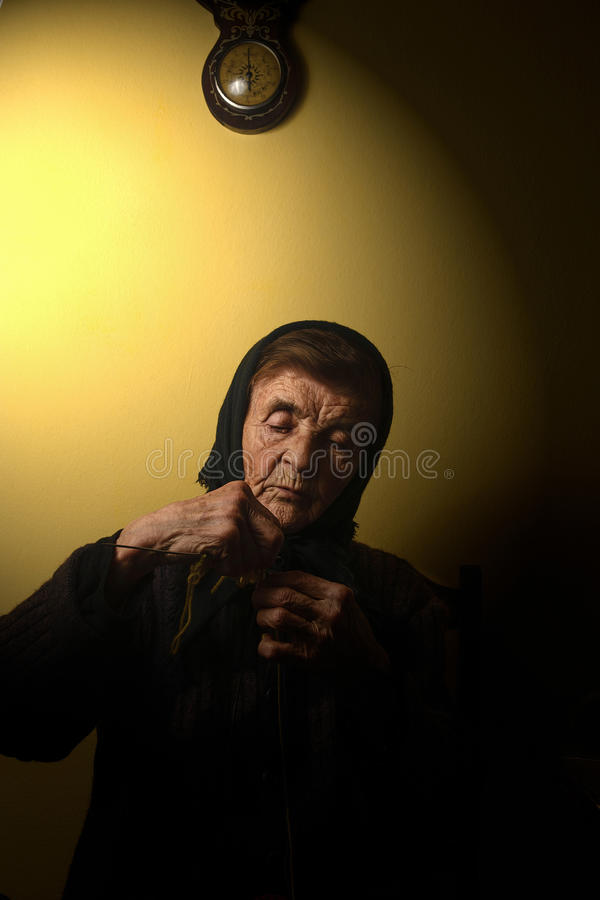 Grandmother with a headscarf is knitting. Low key photograph. royalty free stock photo