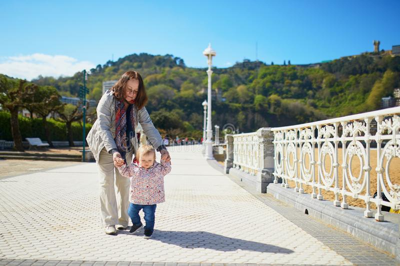 Grandmother helping granddaughter make her firts steps. Middle aged women with little girl on the sea embankment. Toddler learning how to walk royalty free stock photography