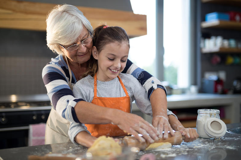 Grandmother helping granddaughter to flatten dough royalty free stock image
