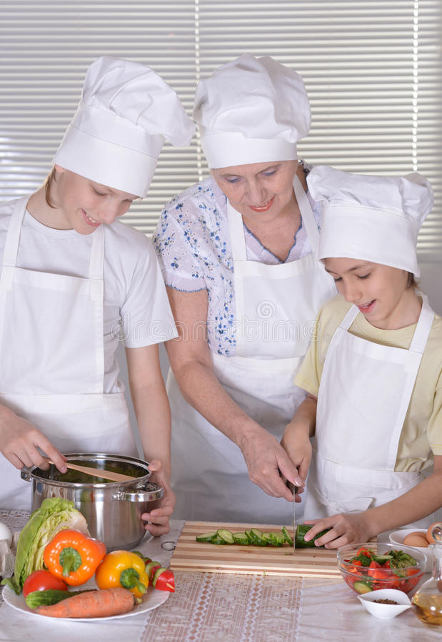 Grandmother and her grandchildren cook royalty free stock photography