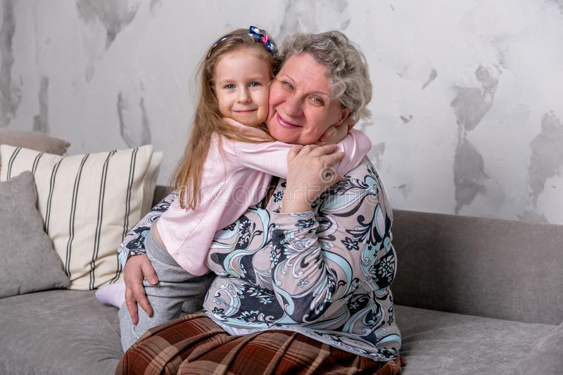 Grandmother and her little granddaughter are watching movies together and playing on the device while sitting on the sofa. Grandmother and her little royalty free stock photography