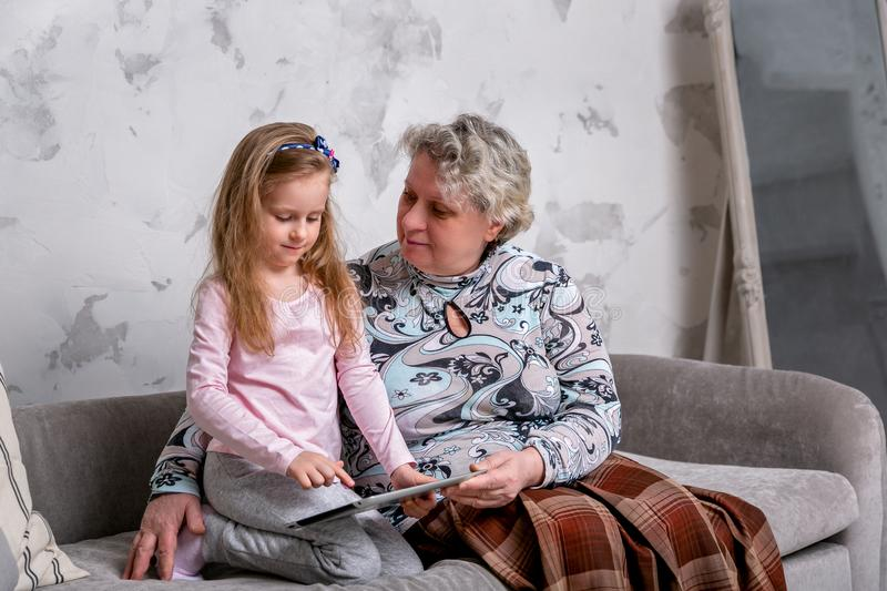 Grandmother and her little granddaughter are watching movies together and playing on the device while sitting on the sofa. Grandmother and her little royalty free stock image
