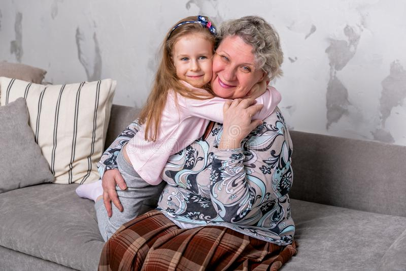 Grandmother and her little granddaughter are watching movies together and playing on the device while sitting on the sofa. Grandmother and her little stock photography