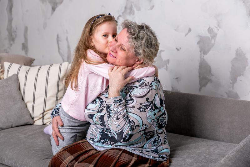 Grandmother and her little granddaughter are watching movies together and playing on the device while sitting on the sofa. Grandmother and her little royalty free stock images