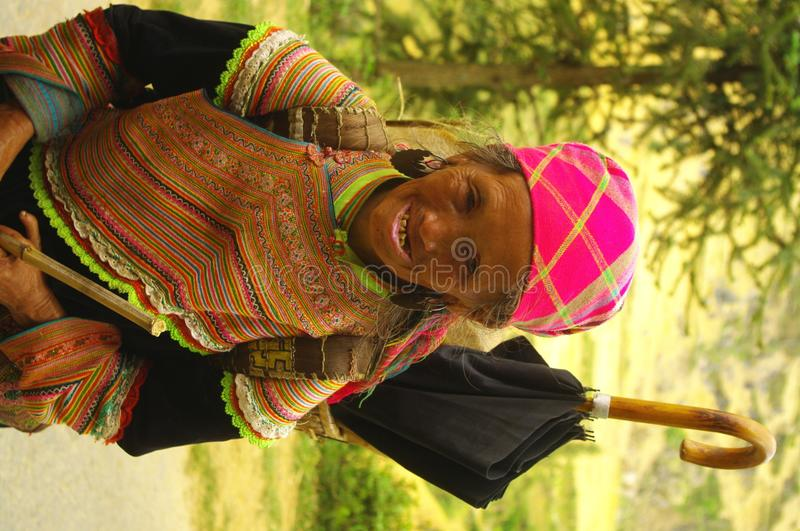 Grandmother Hmong flower. Hmong woman back from the flower market of Muong Khuong. Basket loaded, the eternal umbrella for sun protection such as thunderstorms royalty free stock photos