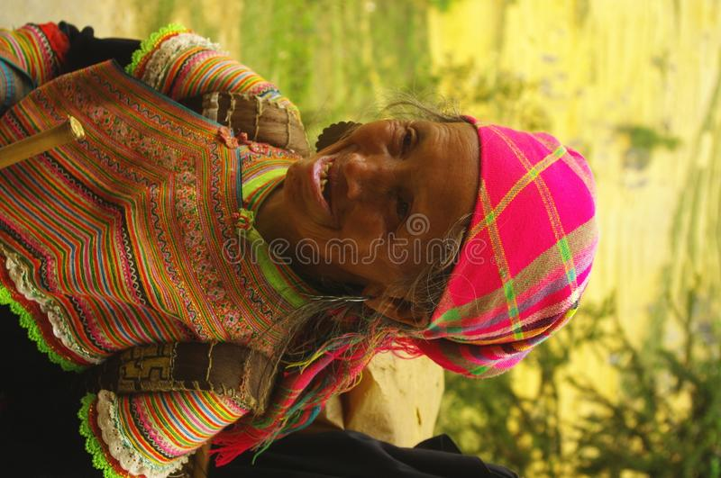 Grandmother Hmong flower. Hmong women back from the flower market of Muong Khuong. Basket loaded, the eternal umbrella for sun protection such as thunderstorms royalty free stock photo