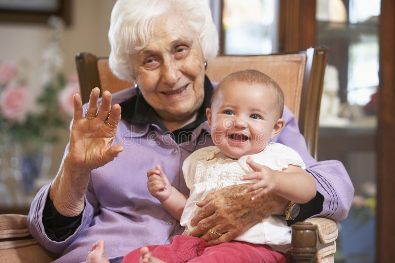 Grandmother holding her granddaughter on lap stock photos