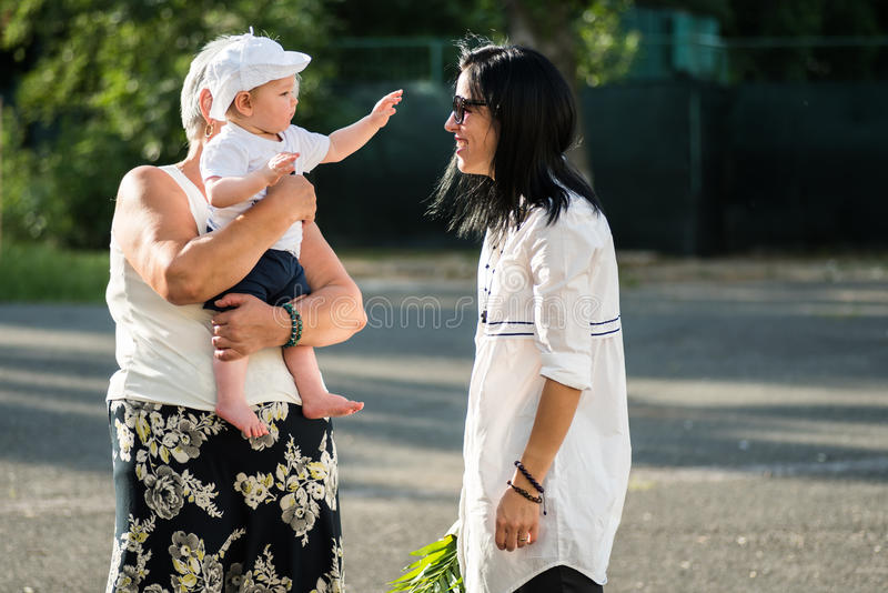 Grandmother holding her nephew in her arms, outdoors royalty free stock photos