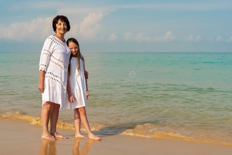 An elderly woman in a white dress with a beautiful girl in a white dress on the sea. Concept of sunny and happy summer stock images