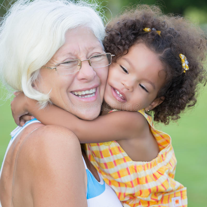Grandmother hugs her hispanic granddaughter stock images