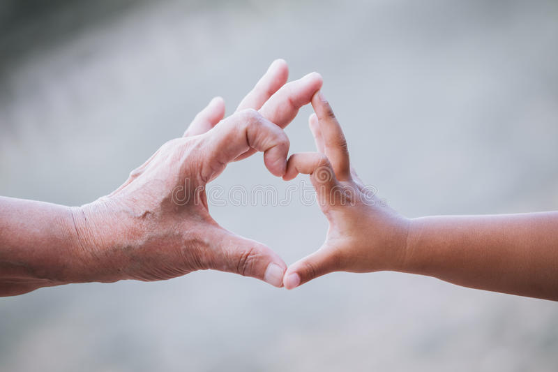 Grandmother and kid little girl making heart shape with hands stock image