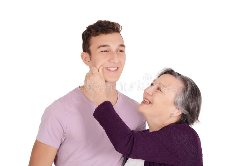 Grandmother kissing her teen grandson on the cheek. Family concept. Isolated white background royalty free stock image