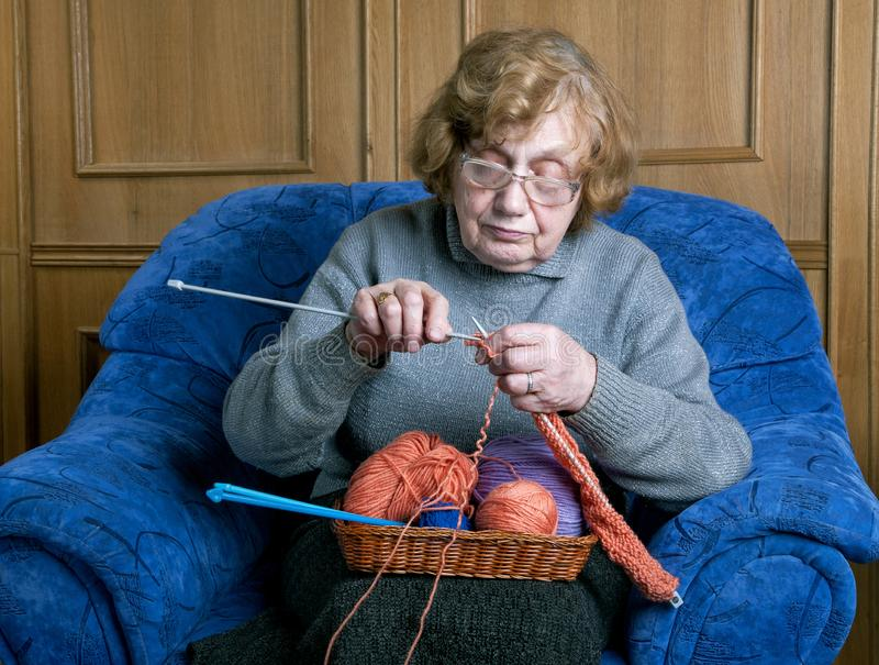 Grandmother knits with knittings in a room. Sitting royalty free stock image