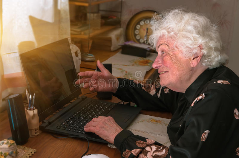 Grandmother learns to work at home on the computer. Happy merry grandmother learns to work at home on the computer and internet stock photo