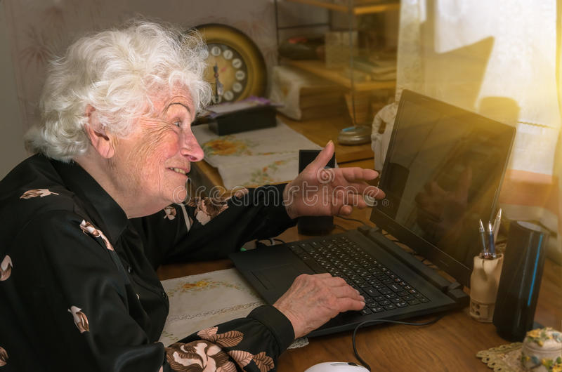 Grandmother learns to work at home on the computer. Happy merry grandmother learns to work at home on the computer and internet royalty free stock photo