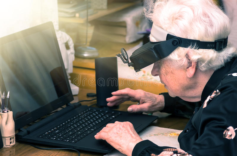 Grandmother learns to work at home on the computer. And internet In big special glasses virual reality stock image