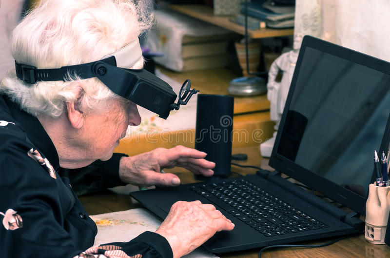 Grandmother learns to work at home on the computer. And internet In big special glasses virual reality stock photo