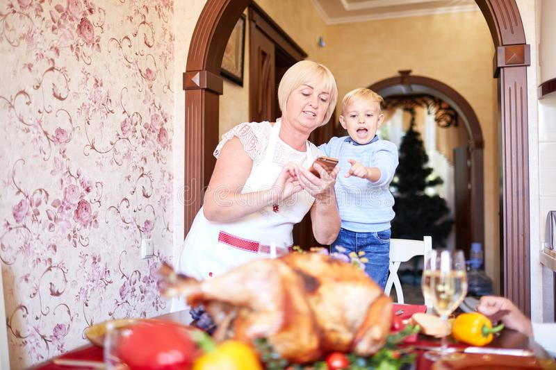 Grandmother and little boy having fun on Thanksgiving on a blurred background. Family holidays concept. Gorgeous modern grandmother having fun with a funny royalty free stock photo