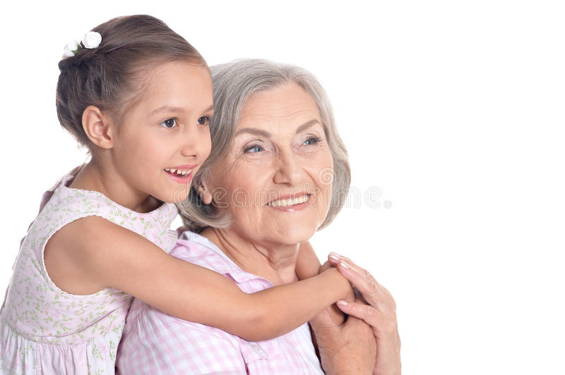 Grandmother and little granddaughter on white background. Portrait of grandmother and little granddaughter on white background stock photo
