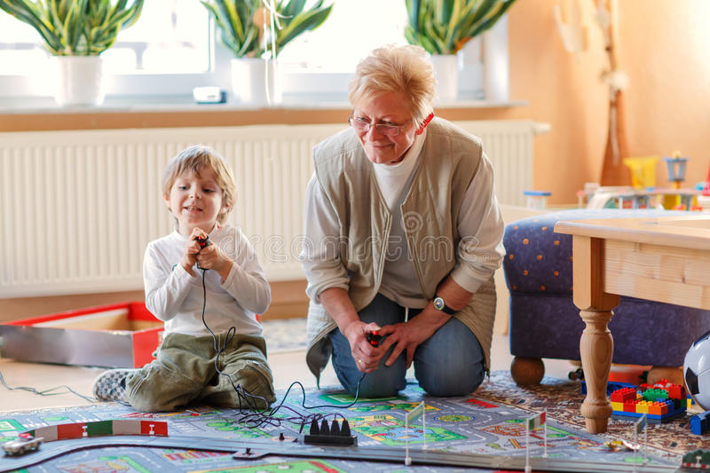 Grandmother and little grandson playing with racing cars. Happy family of two: Grandmother and little grandson playing with racing cars on racetrack, indoors royalty free stock photography