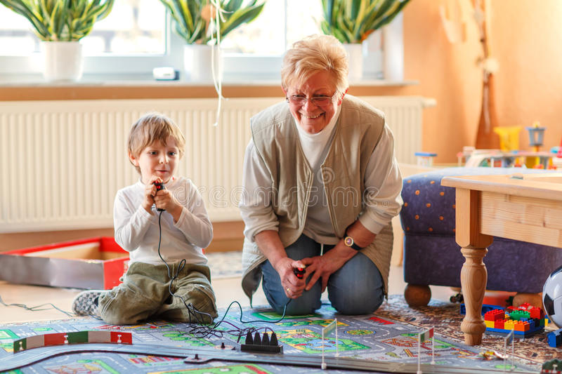Grandmother and little grandson playing with racing cars. Happy family of two: Grandmother and little grandson playing with racing cars on racetrack, indoors royalty free stock images