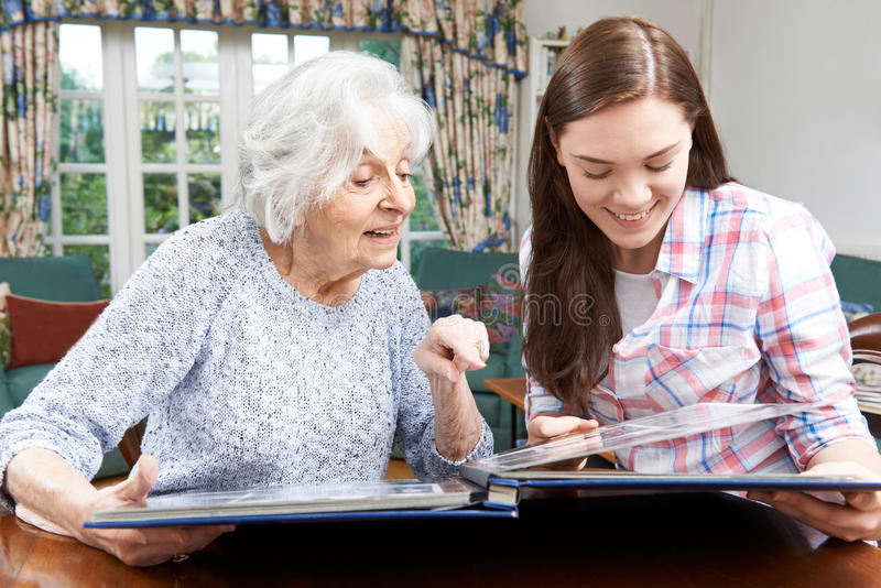 Grandmother Looking At Photo Album With Teenage Granddaughter. Grandmother Looking At Photo Album With Granddaughter stock image