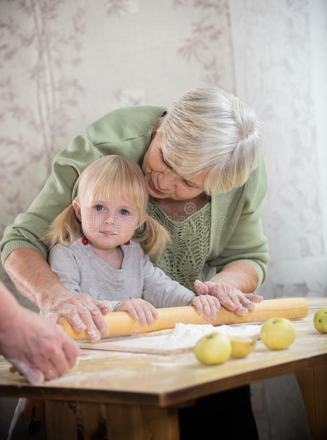 A grandmother making little pies with her granddaughter. Rolling the dough stock image